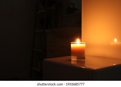 aromatic scented candle glass is put on the white tile shelf in a luxury white bathroom toilet to creat relax and cozy and clean ambient during using