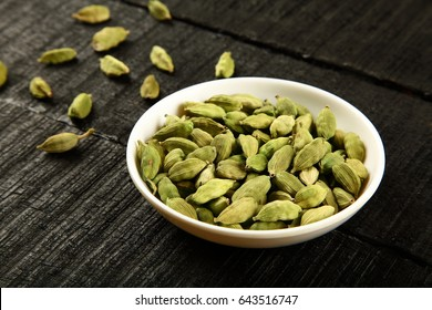 Aromatic spice-Fresh green cardamom on a wooden background.