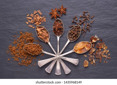 Aromatic spices and brown sugar in silver spoons on black stone background