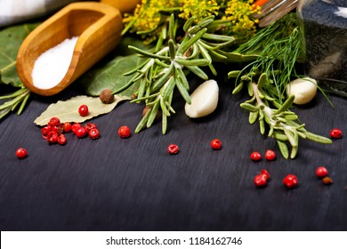Aromatic spices for canning vegetables on a dark background.