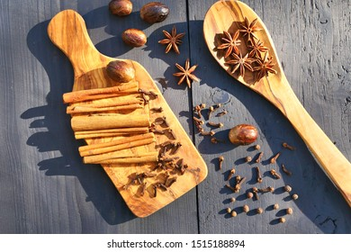 Aromatic spices on wooden board and spoon. Star anise, nutmeg, cloves, allspice and cinnamon sticks