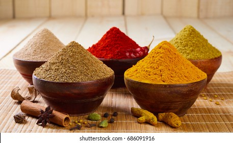 Aromatic spices on wooden bowls. Food ingredients.