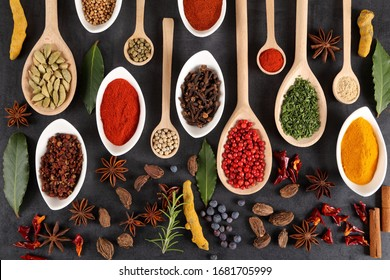Aromatic spices on wooden spoons and ceromic bowls on a dark background. Top view.