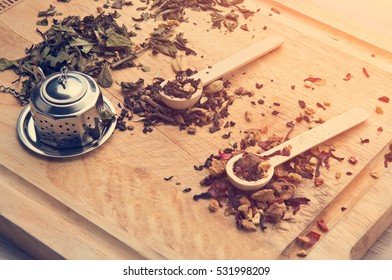 AROMATIC TEA LEAVES SITTING ON WOOD NEXT TO METAL TEA STRAINER WITH MORNING SUN BRINGING JOY, CALMNESS AND HAPPINESS FOR THE SOUL VINTAGE TONE CONCEPT WITH LOOSE FRAGRANT TEA