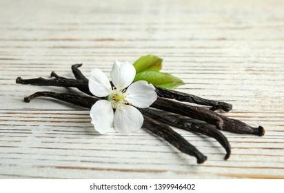 Aromatic vanilla sticks and flower on wooden background