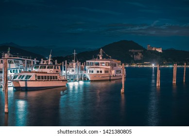 Arona, Italy - 07 29 2015: Harbor of Arona on Lake Maggiore with boats and the Angera Castle on th background with moonlight at night
