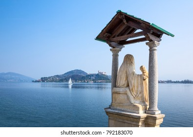Arona, Italy - April 18, 2013:  The statue of the Madonna with Child on the shore of the Maggiore lake with the Borromea fortress of Angera in the background