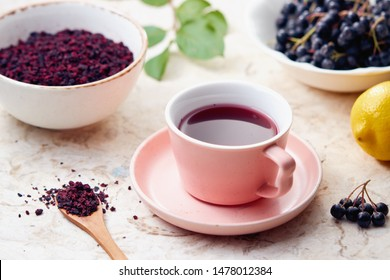 Aronia berry tea  in a cup. Dried aronia berries are commonly used to make antioxidant-rich herbal tea.