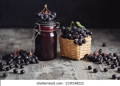 Aronia jam next to fresh berries. Homemade aronia jam in glass jar with fresh aronia berries on wooden table.