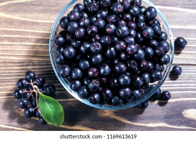 Aronia melanocarpa or black chokeberry in glass bowl on wooden table. Top view.