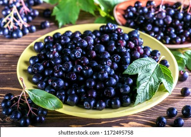 Aronia melanocarpa or black chokeberry with leaves in yellow bowl on wooden background.