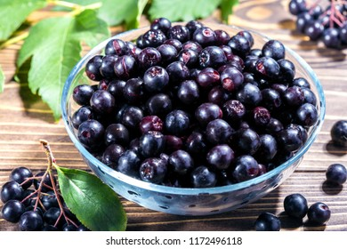 Aronia melanocarpa or black chokeberry with leaves in bowl on wooden background. Healthy food.