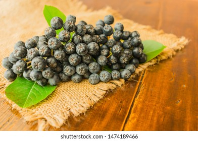 Aronia melanocarpa (Aronia melanocarpa) on a napkin on a wooden table, berries of healthy aronia.