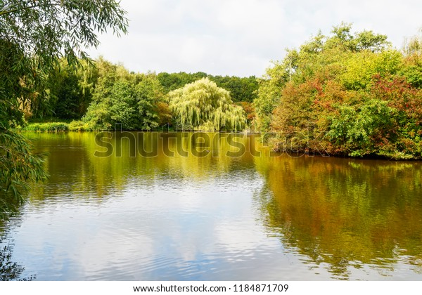 Around the almost flat waters of a small lake the trees and shrubs begin to wear their autumn colours. The weak late summer sky is reflected in the water.