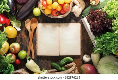 Around empty cookbook a set of healthy food on wooden table, top view