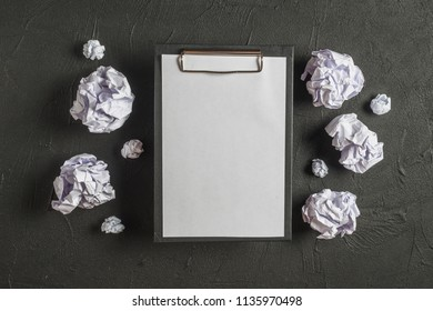 Around the notepads lies lot crumpled paper