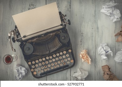 Around the old typewriter crumpled sheets of paper scattered