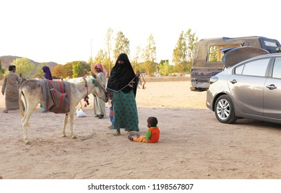 Around Ras Ghareb,Egypt.09.07.2018.A muslim woman,wearing niqab,with her children and a donkey,waiting for some donation from tourists in a car park on the road between Cairo and Hurghada.