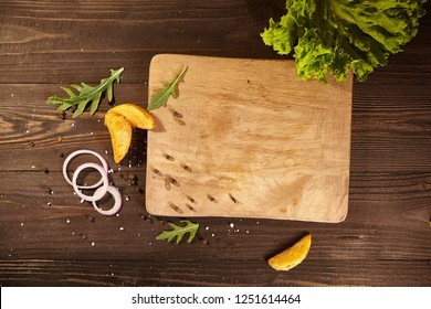 around wooden board scattered potatoes, onions, lettuce, arugula, pepper. Free space for text. Wooden background for food design or restaurant menu. Flatlay.