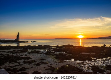 Arousa estuary at golden sunset with the ruins of Saint Saturnino tower, defensive against the Viking invaders, in Cambados city