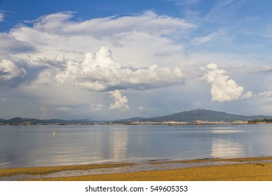 Arousa estuary and Xiabre Mount from Aguiuncho beach in Arousa island with cumulus and cumulonimbus clouds on the sky
