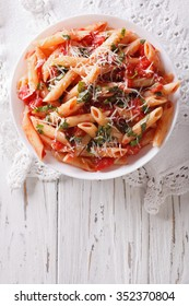 Arrabiata pasta penne with Parmesan cheese on a plate. vertical top view