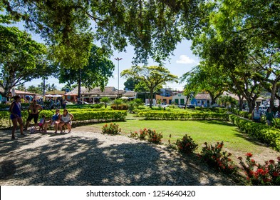 Arraial D'Ajuda/Porto Seguro/Bahia/Brasil - January 02, 2018: Square with trees and people in the center of Arraial D'Ajuda. Colorful shops and homes seen in the background. Tourist spot.