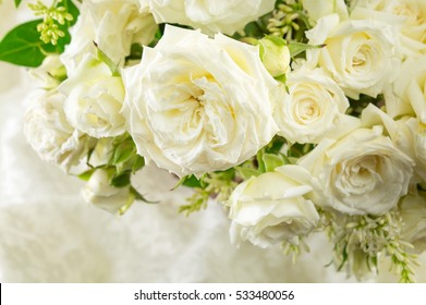 arranged bouquet of white roses on a white cloth