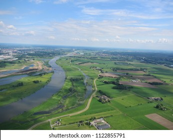 Arranged green agricultural fields near Zwolle in Overijssel Region - Netherlands - with an aerial paragliding perspective on a slightly cloudy Spring day over a quiet river