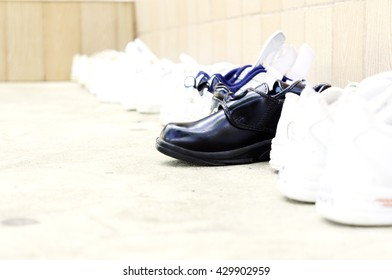 Arranged in an orderly school students shoes before entering the classroom in Thailand, but there is another one. Unique