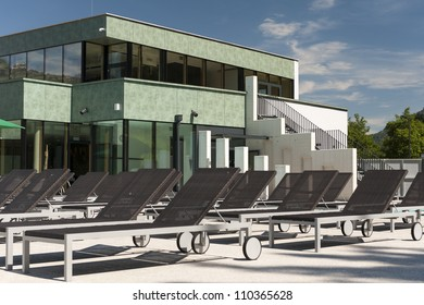 arranged sun loungers in front of a new modern swimming bath