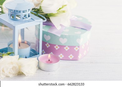 Arrangement of blue lantern, white eustoma flowers, pastel gift box and pink lit candle. Greeting card for holidays