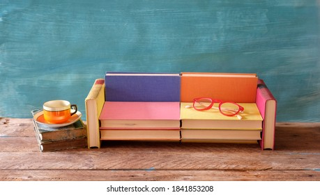 Arrangement of books, coffee and spectacles and a sofa. Reading,literature,education,relaxation concept, good copy space.