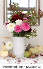 arrangement with bouquet of dahlia flowers, pumpkins, an apple and nuts