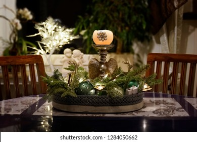 A arrangement with candle and green fir branches decorates a room at Christmas time. Dark wood furniture and a window with plaster angels and illuminated tree.