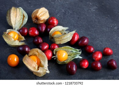 Arrangement of cape gooseberries - physalis with cranberries on slate with copy space