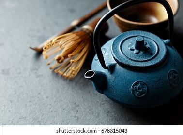 An arrangement of a cast iron tea pot and tea whisk. Asian culture. Close-up