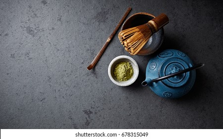 An arrangement of a cast iron tea pot, matcha powder and tea whisk; Flat lay; Copy space; Asian culture
