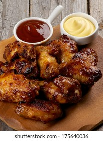 Arrangement of Chicken Legs and Wings Barbecue with Ketchup and Cheese Sauces on Wooden Plate closeup