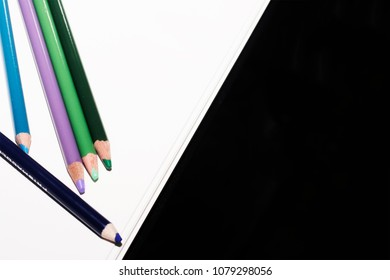An arrangement of cool colored pencils on a paper white background