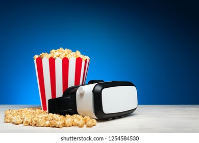Arrangement of crispy golden popcorn in striped bucket and glasses of virtual reality on blue background