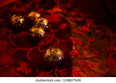 Arrangement of different christmas elements on a festive red cloth. Illuminated by candlelight focus and narrow depth of fiel