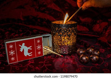 Arrangement of different christmas elements on a festive red cloth. Illuminated by candlelight focus and narrow depth of field