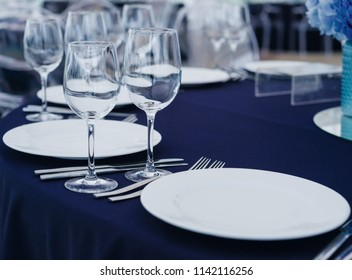 Arrangement of empty elegant tableware and silverware with wine glasses and flower decor on blue tablecloth