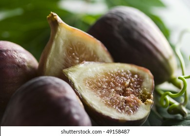 Arrangement of figs on green leaves with blurry background