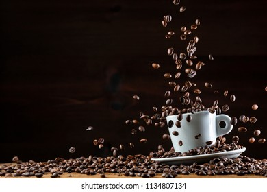 Arrangement of flying roasted dark coffee beans in white ceramic cup against black background