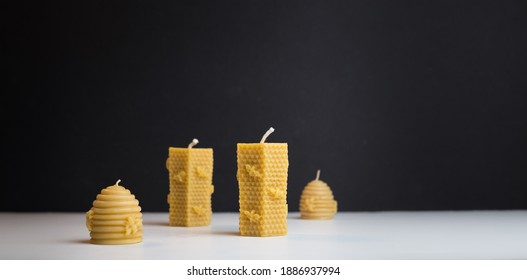 Arrangement of four beeswax candles, two large and two small.  White surface with dark background, small unlit brand new candles ready for use in home decor.