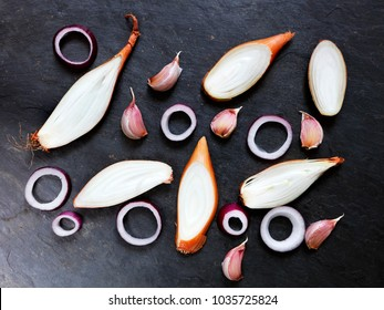 Arrangement of French Echalion Shallots, garlic and red onion on slate