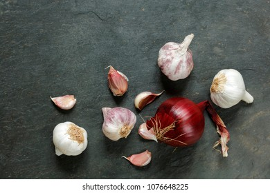 Arrangement of garlic and onions on a natural slate table with copy space