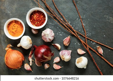 Arrangement of garlic and onions with pepper spices on a natural slate table with twigs